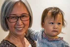 A silver-haired Asian woman with glasses holds an infant in her arms and looks smilingly at the camera.