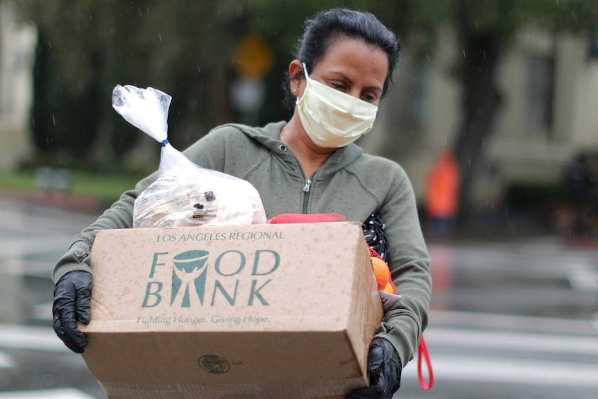 A woman in a face mask carrying a box of food