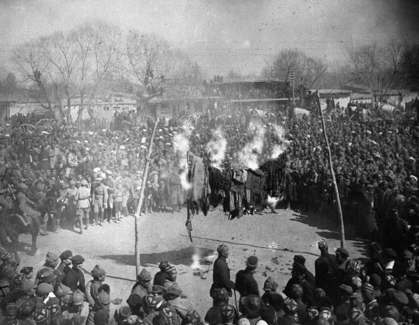 Black and white photograph of a crowd watching women burn their veils on International Women's Day in Uzbekistan in the 1920s