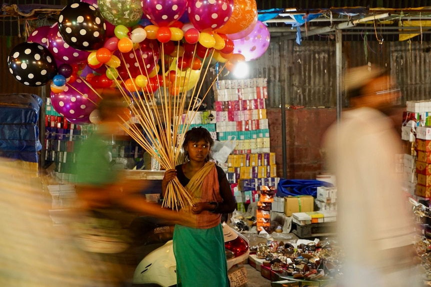 A young girl holding a bunch of balloons walks down a busy street at night.