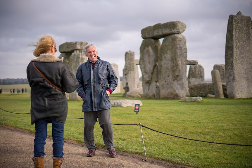 A tourist poses for a photo at Stonehenge.