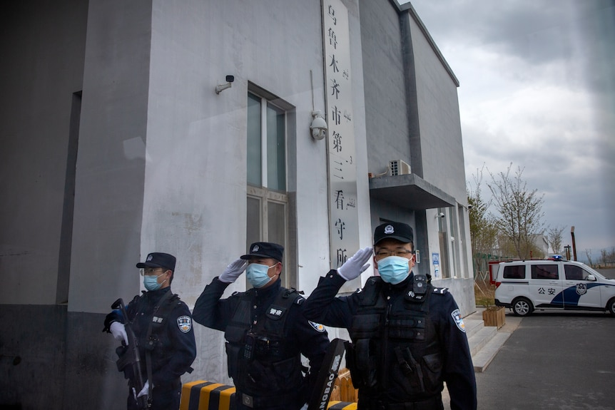 Police officers salute at the outer entrance of the detention centre