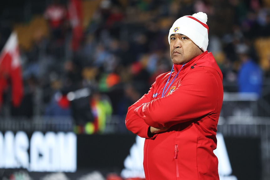 Toutai Kefu stands with arms crossed, wearing a beanie and red jacket.