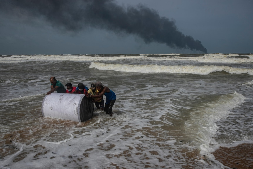 Locals salvage a container washed to shore from the burning ship