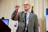 Rainer Weiss holds a piece of equipment that looks like a metal cylinder attached to orange strings.