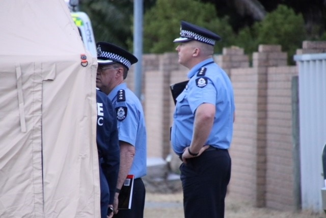 Two police officers in uniform stand next to a canopy on a suburban street.