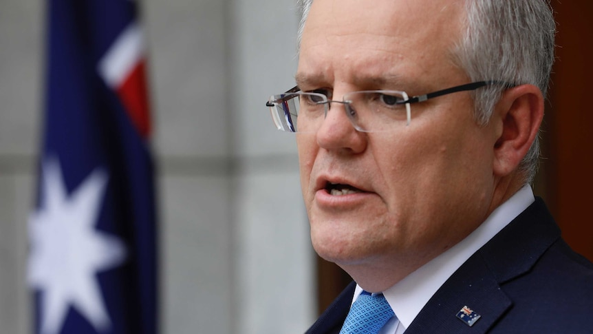A close up of Prime Minister Scott Morrison, he is wearing a suit and pinned Australian flag broach.