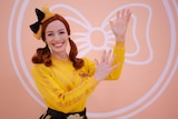 Female red haired children's entertainer wearing bright yellow top conducting sign language.