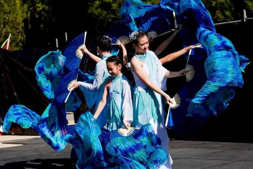 Chinese dancers with bright blue fans.