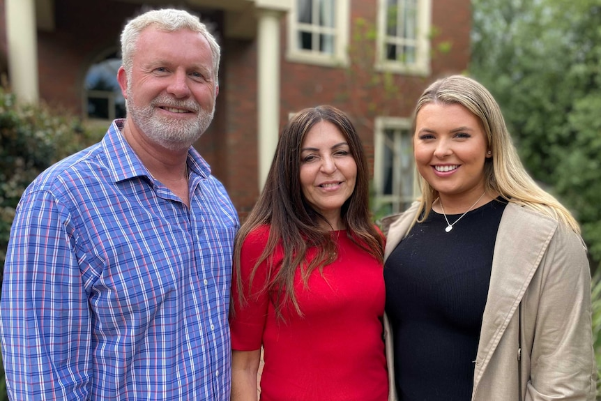 A man with grey hair and a beard stands with a dark haired woman and her blonde daughter.