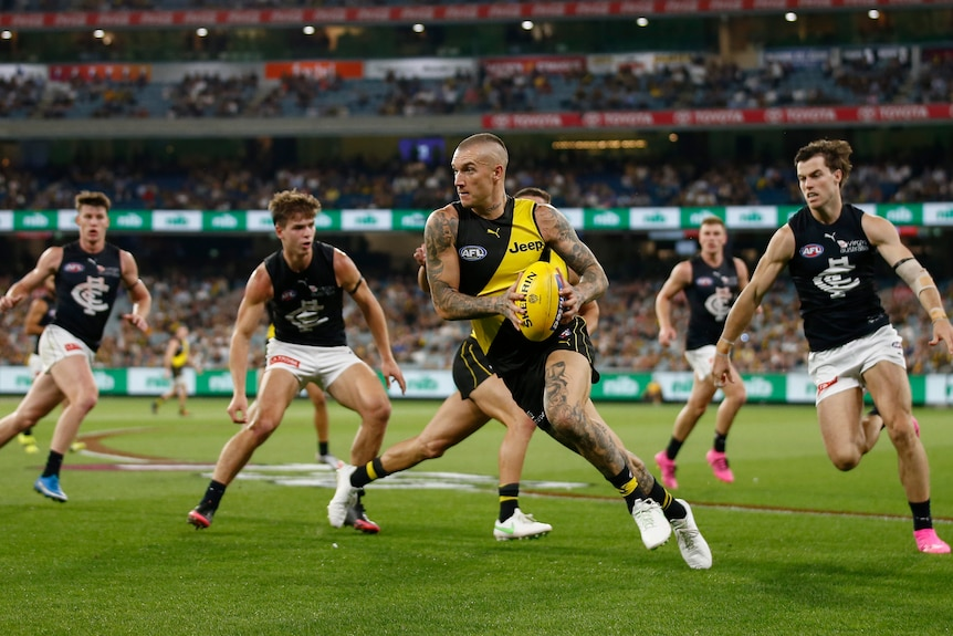 Dustin Martin carries the ball while running. He's surrounded by four Carlton players