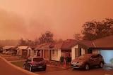 bushfire smoke can be seen rising behind houses in suburban Port Macquarie