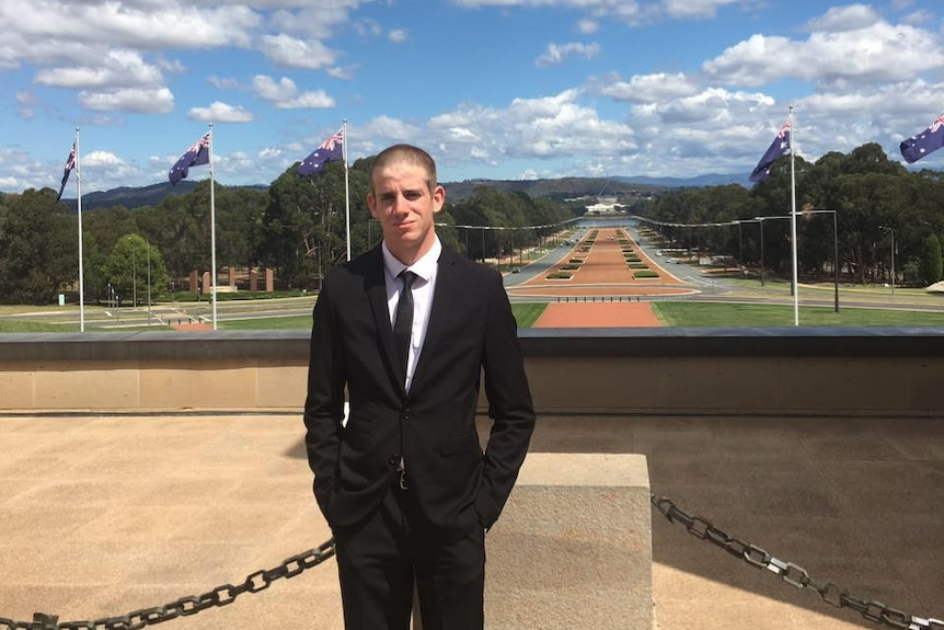 Liam Wolf standing on Federal Parliament forecourt with Anzac Parade and War Memorial behind him