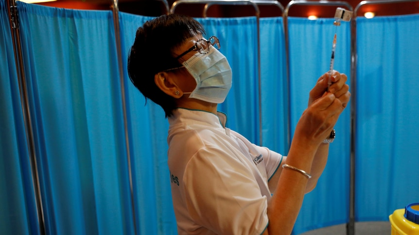 A nurse in a surgical mask holds up a syringe with a hospital curtain in the background.