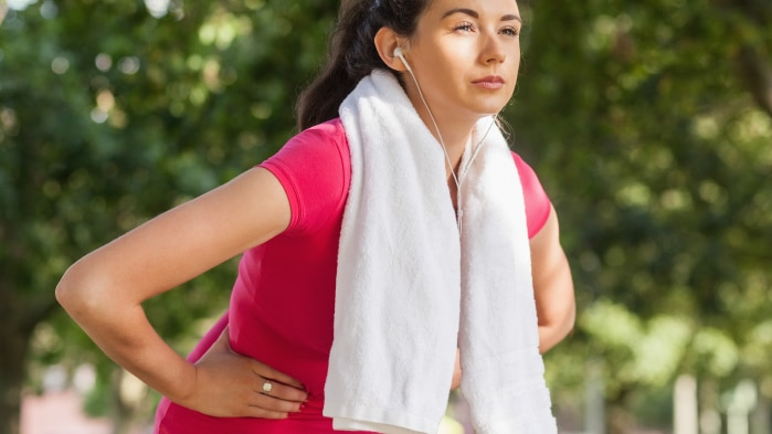 Woman with towel around neck bent over with hands on torso