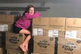 A woman sits on top of two pallets of boxed toilet paper
