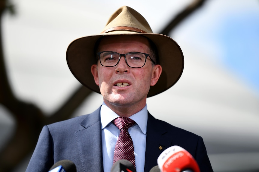 a man in a hat and suit speaking to the media