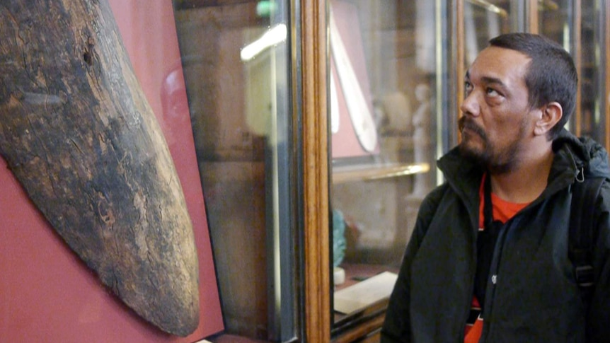 An Indigenous man looks at a centuries-old shield in a museum.