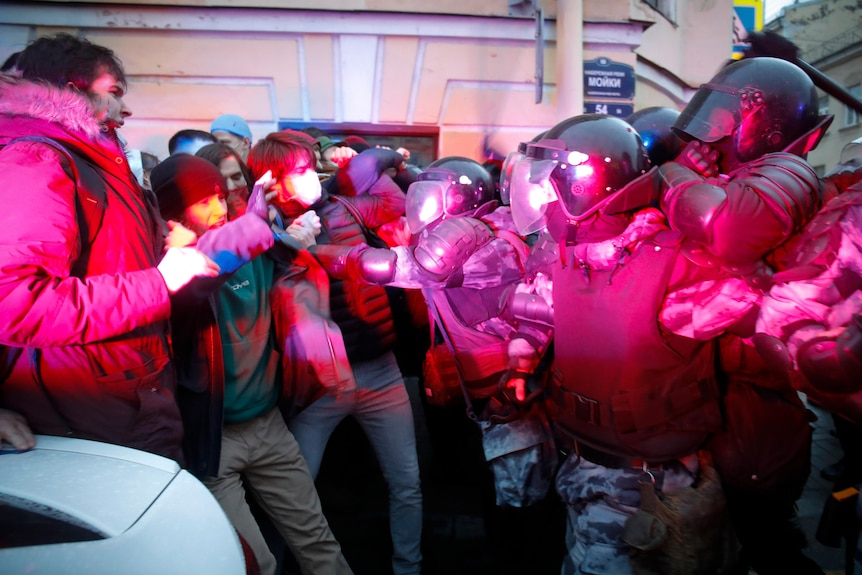 People clash with a line of riot police in a red lit setting.