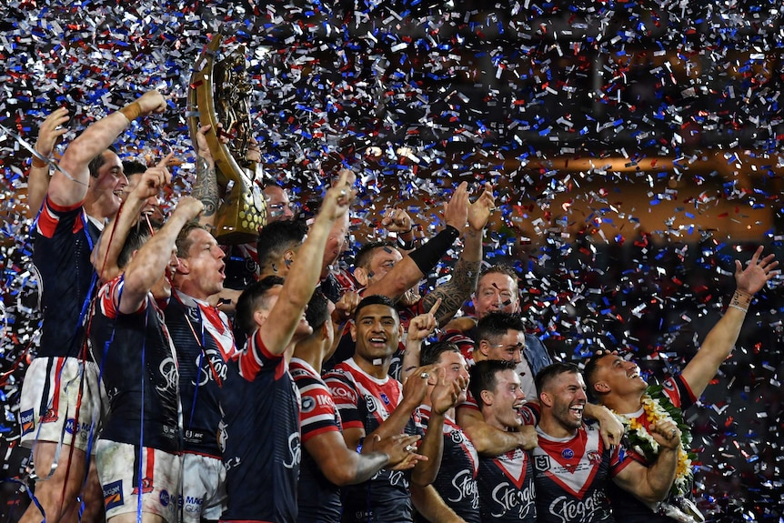 The Sydney Roosters lift the NRL trophy as glitter rains down.