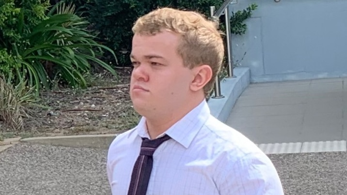 Photo of young man in white shirt with black dress tie walking away from camera.