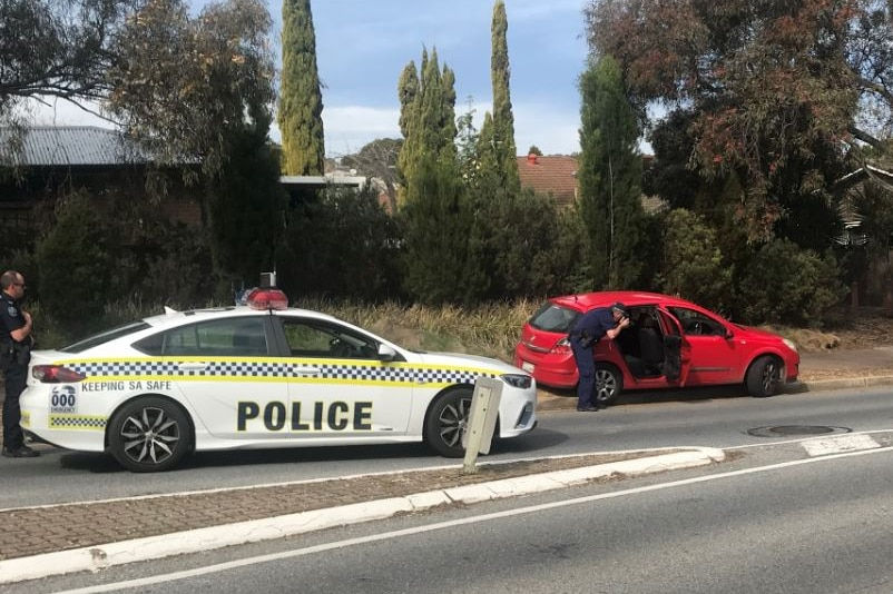 A police car parked on a road behind a red vehicle with a police officer looking inside