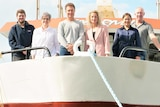 Six people in row, man, woman, man, woman, woman, man standing up high on the bow of a tuna boat looking down to camera