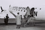 A black and white photo of a man getting off a United Nations plane