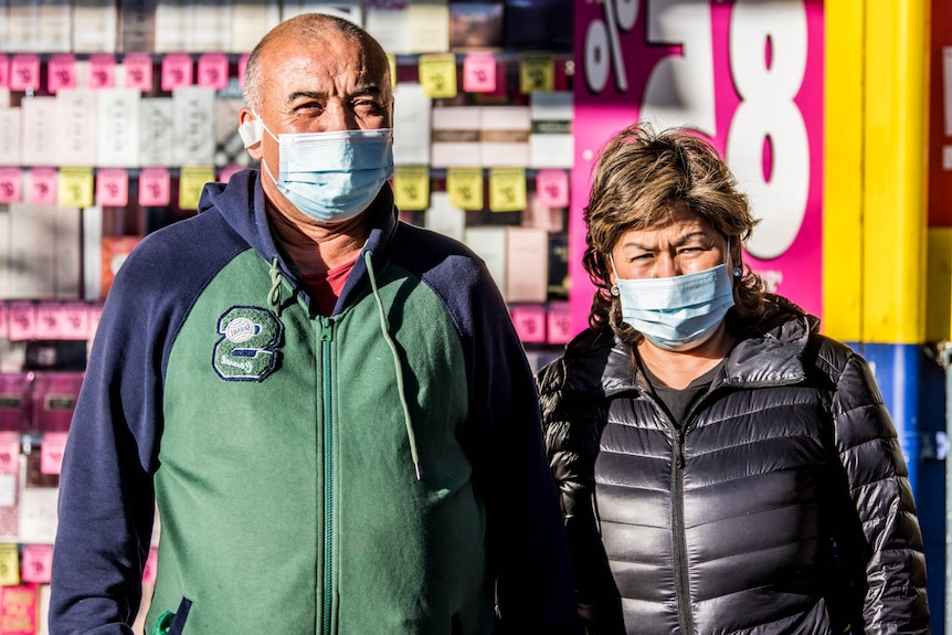 Two people wearing masks on the street