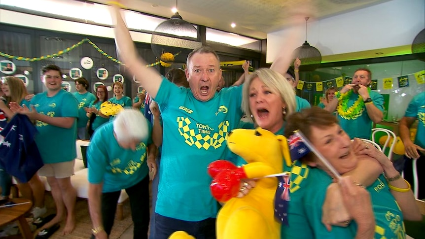 A man with his arms in the air and a woman crying holding a yellow kangaroos and an Australian flag
