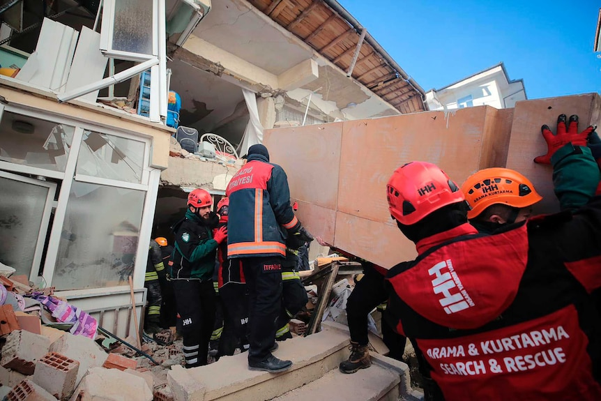 Rescuers work on searching for people buried under the rubble on a collapsed building in Elazig.