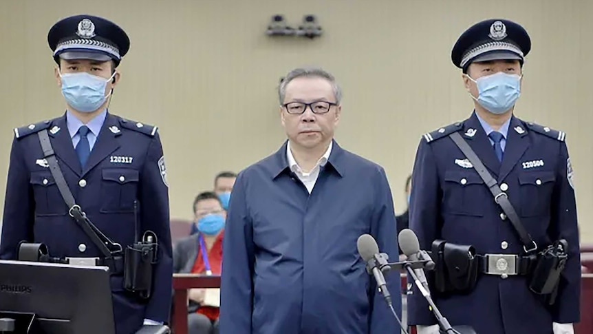 A man in glasses stands between two guards wearing masks.