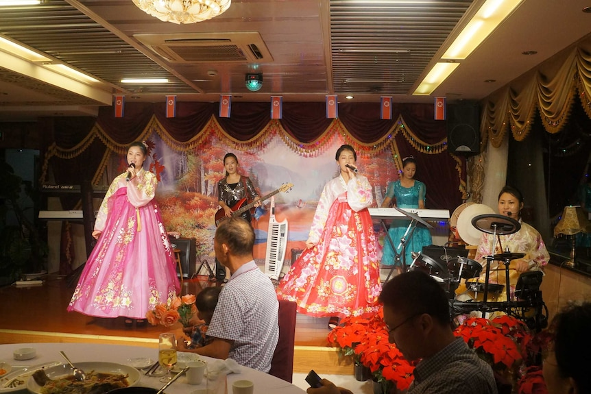 North Korean waitresses in bright traditional clothes perform on a stage.
