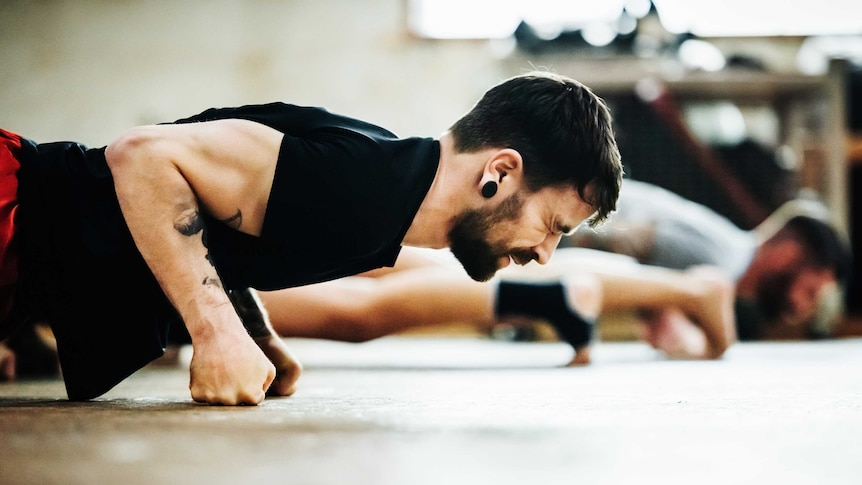 Close-up shot of a muay thai boxing athlete doing push-ups in a gym.