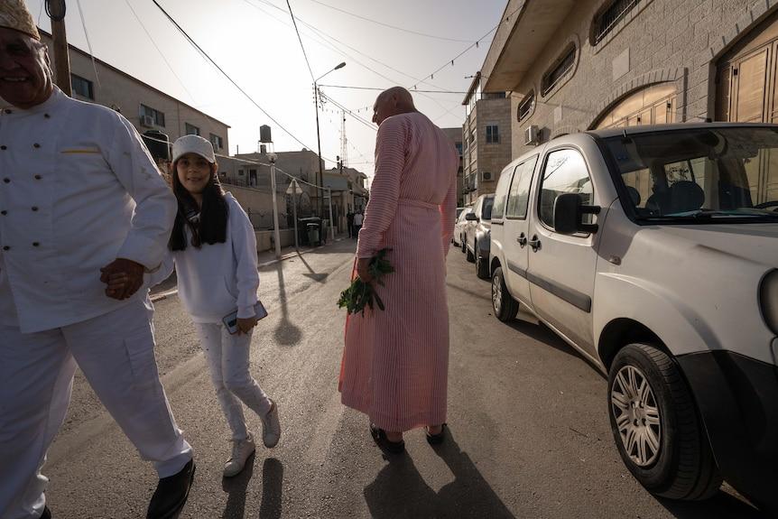 Niña vestida de blanco sonriendo mientras sostiene la mano de un anciano