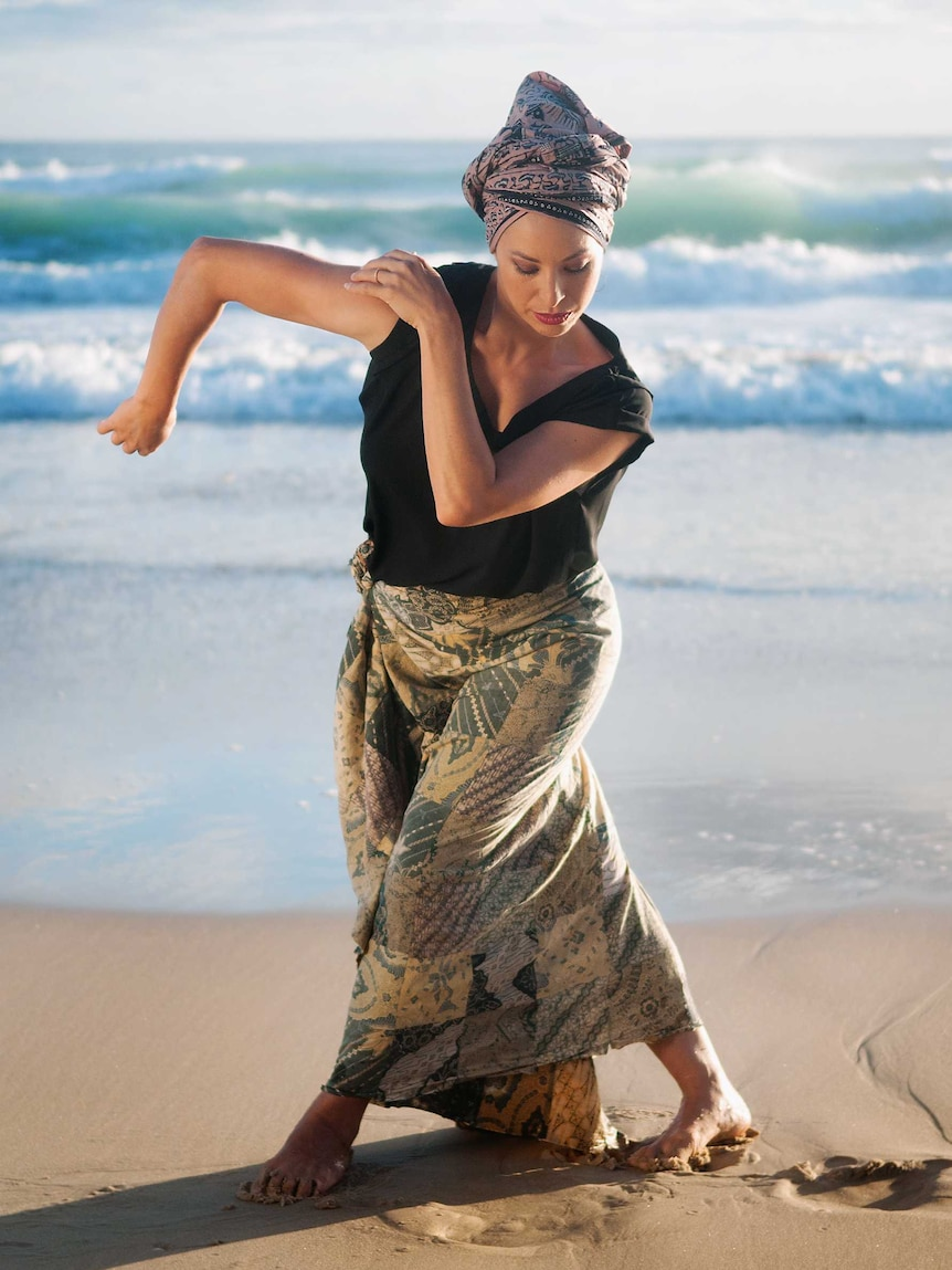 On a bright day, you view a woman in a traditional Indonesian dance pose on the beach.