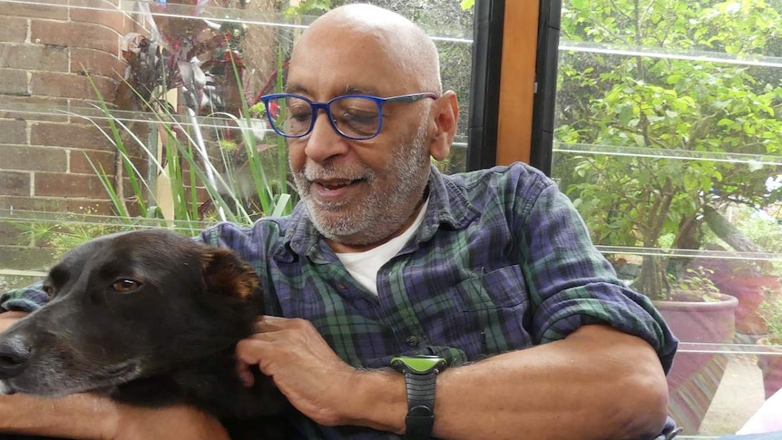 Paul van Reyk sits on a couch with his arm around a black dog
