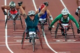 A wheelchair athlete raises her arms as she rolls over the finish line in Sydney's Olympic stadium.