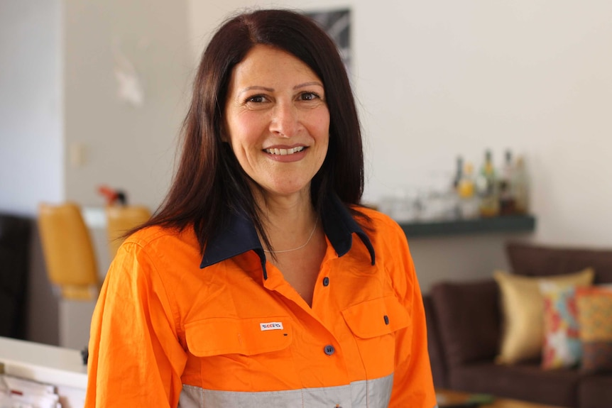 Corinne Brown wearing a fluoro shirt and smiling at camera