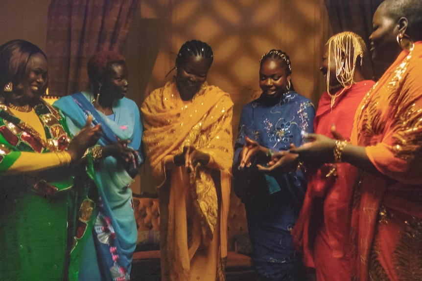 A video projection of six African women standing in bright dresses and smiling, their hands pressed together as if mid-clap