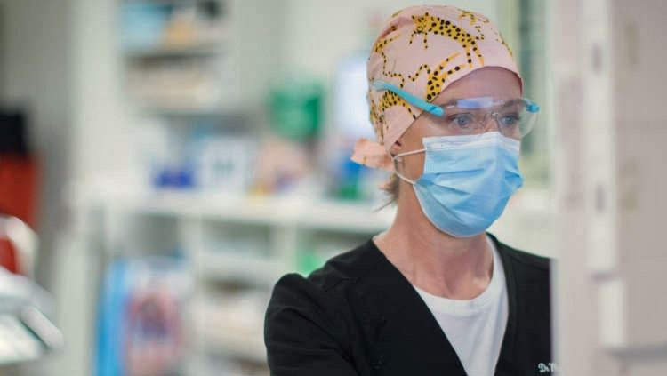 A woman wearing a surgical cap, mask and glasses works on a computer.