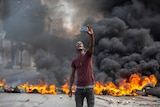 Man takes a selfie in front of fire