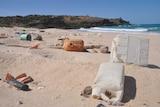 trash lies across a remote beach