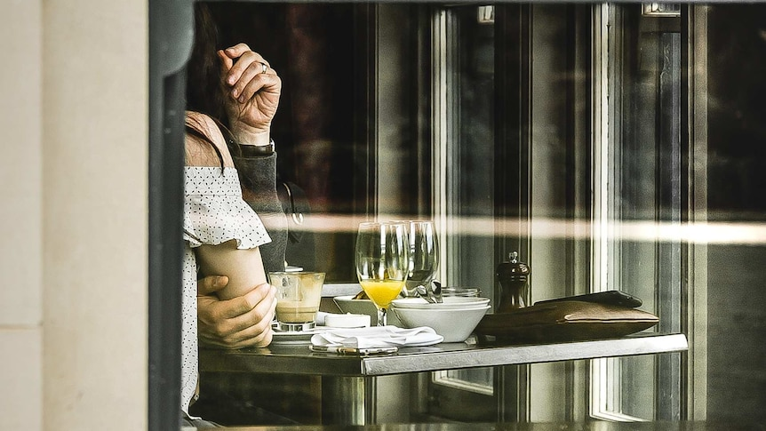 A man's hand is touching the arm of a woman as they sit at a table together representing a employee employer sexual relationship