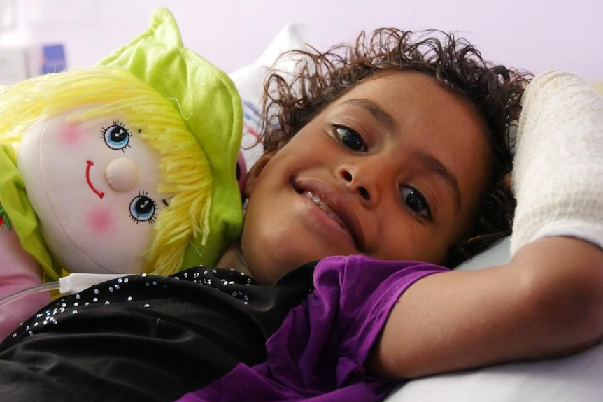 A smiling child with a bandaged arm and a colourful doll in a hospital bed