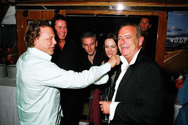 A man in a white shirt adjusts the collar of another man as three people watch on smiling