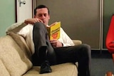 Don Draper from the TV show Mad Men reads a copy of Portnoy's Complaint.