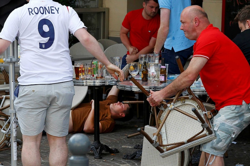 An England fan lies stricken on the ground after clashes with Russian supporters