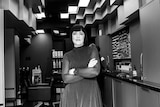 Black and white image of a women with her arms folded in a hair salon