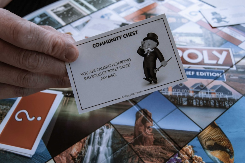 "Community Chest card from Australian Monopoly Board game reading, ""You are caught hoarding 240 rolls of toilet paper! Pay M50."""